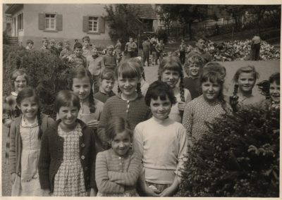 Auf dem Foto posieren Schülerinnen und Schüler am Rande des Schulhofs bei der Alten Schule, damals Volksschule genannt