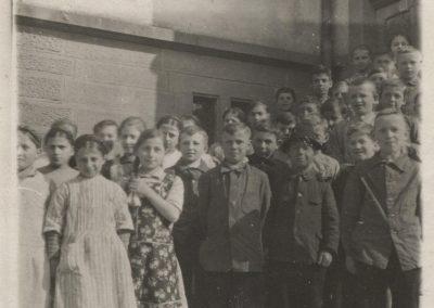 Schülerinnen und Schüler posieren am Treppenaufgang zur Volksschule Dörlinbach (Alte Schule).