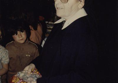 Schwester Fiatis verteilt Schokolade und sonstige Süßigkeiten an die Kinder (1991)