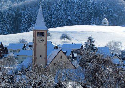 Winter-Impressionen im Januar 2021: Im Vordergrund die Pfarrkirche St. Johannes Dörlinbach, im Hintergrund auf dem Kappelberg die Gedächtniskapelle.