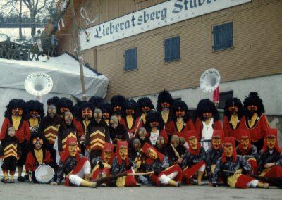 """Winter 1994: Die Bremsdorfer Narrenzunft mit ihren drei Gruppen vor der Kulisse der Berggaststääte """"Lieberatsberg Stuben""""."""