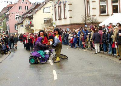 """Impressionen vom Narrenumzug im Februar 2004 in Dörlinbach: Kräftemessen zwischen einer motorisierten """"Schluchwaldhexe"""" und dem """"Bremmedatscher""""."""