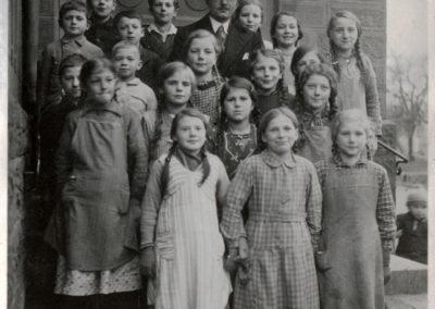 Schulklasse präsentiert sich mit ihrem Lehrer auf der Treppe zum alten Schulhaus (1938).