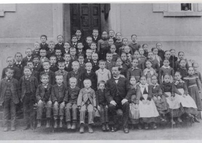 Hauptschullehrer Markus Alfery mit seinen Dorfschulkindern im Jahre 1900 vor dem Schul- und Rathaus in Dörlinbach.