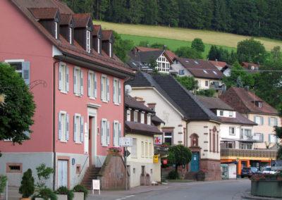 Juni 2021: Blick durch die Hauptstraße. Im Vordergrund das Rathaus, dahinter das Lebensmittelgeschäft Griesbaum, die Alte Schule, das Fachgeschäft Zehnle und das Pfarrhaus. Oberhalb fällt der Blick auf Häuser in der Straße Am Kappelberg.