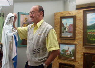 Johann Busch, den alle nur Hans nennen, ist ein Hobbykünstler, der überall im Ort seine Spuren hinterlässt. Sei es durch Wandmalerei, Restaurieren von Statuen, Schilder kunstvoll gestalten oder durch seine vielen Ölgemälde mit heimischen Motiven. Hier präsentiert er sich beim Bauernmarkt 2003 auf dem Parkplatz bei der Alten Schule.