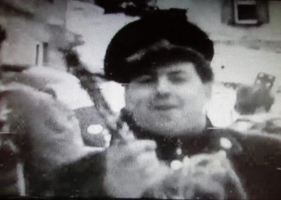 """Filmausschnitt aus """"Derlebacher Rosemaendig 1968 mit Gutselewerfer Oskar"""". Im Fokus der Kamera Hermann Joseph Fischer (1926 bis 1995) in alter Musikuniform."""