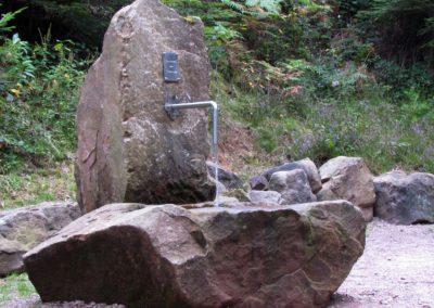 """Beim ehemaligen Dörlinbacher Sandsteinbruch wurde 2017 ein Rastplatz für Wanderer und Spaziergänger eingerichtet. Darauf befindet sich auch ein Sandsteinbrunnen. Er erhielt den Namen """"Brunnen am Totenweg""""."""